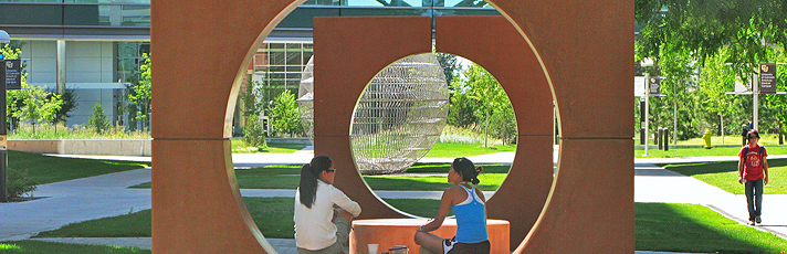 People sitting on sculptures on campus