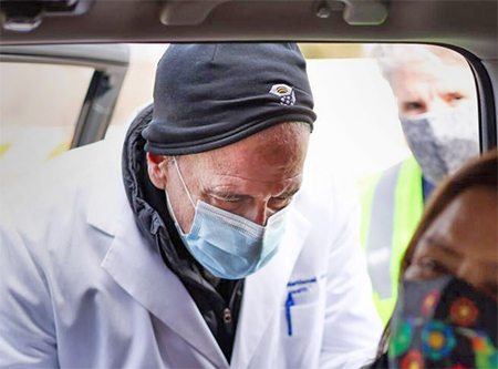National Jewish Health President Michael Salem, MD, administers a vaccine outside St. Cajetan Catholic Church