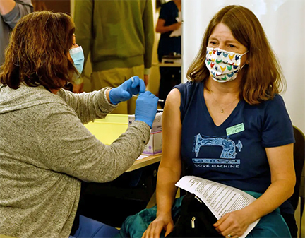 School nurse at Cottonwood Creek Elementary in the Cherry Creek district receives a vaccine