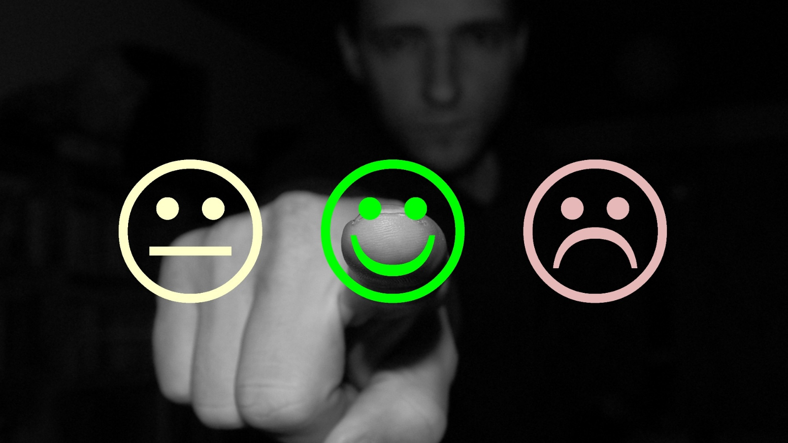 Finger selecting a sad, happy or neutral faces